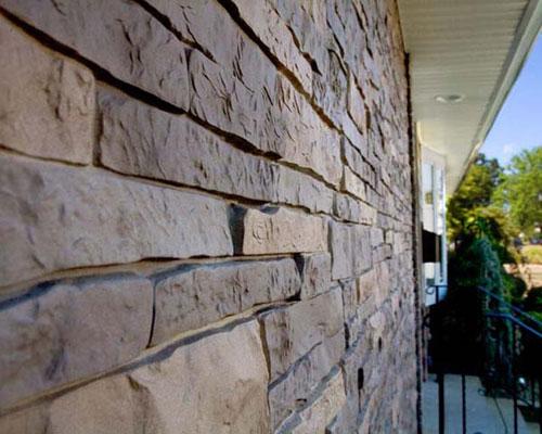 Отделка дома прочными фасадными панелями под камень
